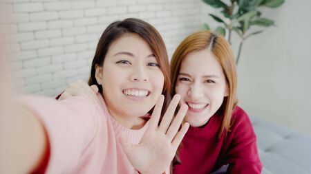Asian blogger women using smartphone selfie and recording vlog video in living room at home, group of friend enjoy funny moment while lying on the sofa when relax at home. Point of view.