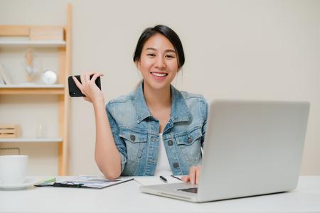 Hermosa mujer de negocios inteligente asiática en ropa casual elegante trabajando en equipo portátil y hablando por teléfono mientras está sentado en la mesa en la oficina creativa. Mujeres de estilo de vida que trabajan en el concepto de hogar. Foto de archivo