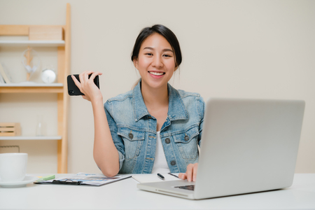 Mooie slimme zakelijke Aziatische vrouw in slimme vrijetijdskleding die op laptop werkt en aan de telefoon praat terwijl ze op tafel zit in een creatief kantoor. Lifestyle vrouwen die thuis werken concept. Stockfoto