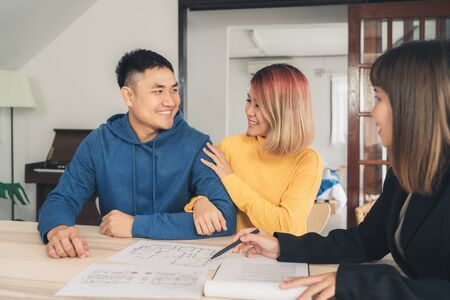 Happy young Asian couple and realtor agent. Cheerful young man signing some documents while sitting at desk together with his wife. Buying new house real estate. Signing good condition contract. 免版税图像