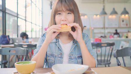 Business freelance Asian woman eating bread and drinking warm cup of coffee while sitting on table in cafe. Lifestyle smart beautiful female relax in coffee shop concepts.