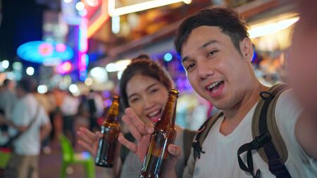 Traveler Asian blogger couple travel in Bangkok, Thailand, sweet couple using mobile phone make vlog and live in social media while hangout at The Khao San Road. Couple travel in Thailand concept.