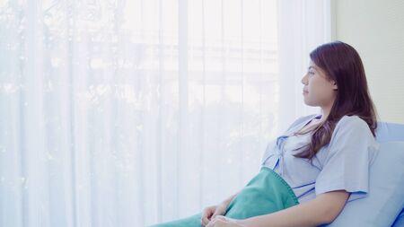 Bella paziente asiatica malata e dorme mentre si trova sul letto del paziente in ospedale. Medicina e concetto di assistenza sanitaria.