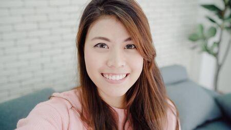 Mujer blogger asiática que usa un teléfono inteligente grabando video de vlog en la sala de estar en casa, la mujer disfruta de un momento divertido mientras está acostada en el sofá cuando se relaja en casa. Blogger de estilo de vida haciendo videos en casa.