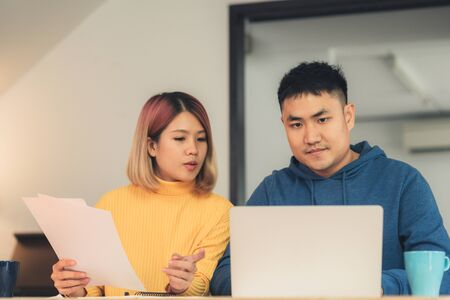 Young asian couple managing finances, reviewing their bank accounts using laptop computer and calculator at modern home. Woman and man doing paperwork together, paying taxes online on notebook pc. Archivio Fotografico - 129692839