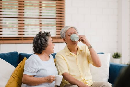 Asian elderly couple drinking warm coffee and talking together in living room at home, couple enjoy love moment while lying on sofa when relaxed at home. Lifestyle senior family at home concept. 版權商用圖片 - 129692840