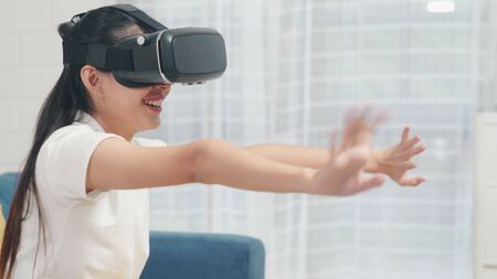 Asian teenager woman using glasses virtual reality simulator playing video games in living room, female feeling happy using relax time lying on sofa at home. Lifestyle women relax at home concept. Stock Photo
