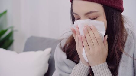 Asian woman feel headache wrapped in grey blanket blow the nose and use tissue while lying on couch when relax in living room at home. Lifestyle women in Christmas and New year holidays concept.