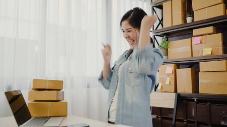 Beautiful smart Asian young entrepreneur business woman owner of SME feeling happy dancing while see business achievement. Small business owner at home office concept.
