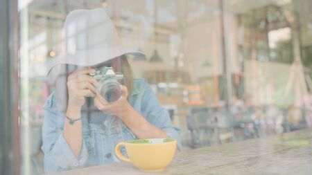 Food blogger Asian woman using camera for photo dessert, bread and drink while sitting on table in cafe. Lifestyle beautiful women relax at coffee shop concepts.