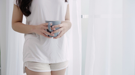Happy beautiful Asian woman smiling and drinking a cup of coffee or tea near the window in the bedroom. Young asia female open the curtains and relax in the morning. Lifestyle woman at home concept.