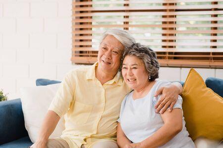 自宅のリビングルームでテレビを見ているアジアの老夫婦は、甘いカップルは自宅でリラックスしたときにソファに横たわっている間、愛の瞬間を楽しみます。家庭のコンセプトで時間ライフスタイルシニアファミリーを楽しんでいます。 写真素材