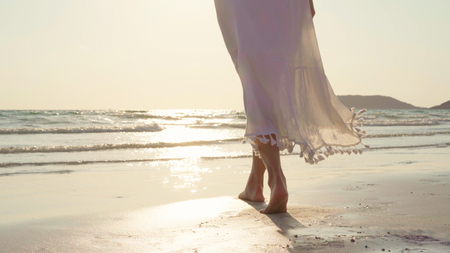 Young Asian woman walking on beach. Beautiful female happy relax walking on beach near sea when sunset in evening. Lifestyle women travel on beach concept. Stock Photo