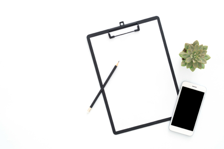 Creative flat lay photo of workspace desk. Top view office desk with phone, pencil, blank clipboard and plant on white color background. Top view with copy space, flat lay photography.