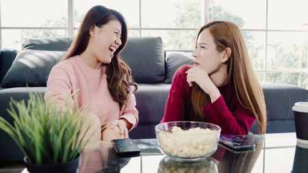 Asian women using smartphone and eating popcorn in living room at home, group of roommate friend enjoy funny moment while lying on the sofa. Lifestyle women relax at home concept. Stock Photo