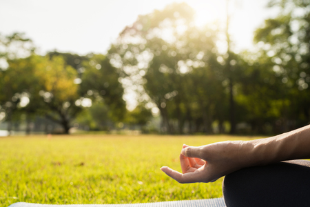 Young asian woman yoga outdoors keep calm and meditates while practicing yoga to explore the inner peace. Yoga have good benefits for health near lake at park. Sport and Healthy lifestyle concept. Banco de Imagens