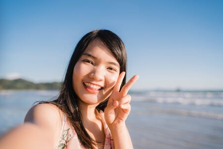 Tourist Asian woman selfie on beach, young beautiful female happy smiling using mobile phone taking selfie on beach near sea when sunset in evening. Lifestyle women travel on beach concept.