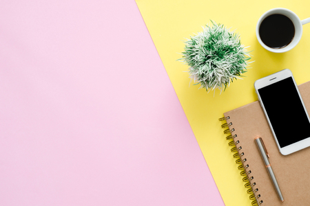Office desk working space - Flat lay top view of a working space with white blank notebook page, coffee cup and mock up phone on pastel background. Pastel pink yellow color background space concept. Stock Photo
