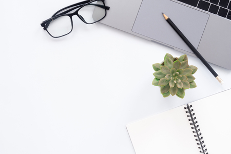 Creative flat lay photo of workspace desk. Top view office desk with laptop, glasses, pencil, notebook and plant on white color background. Top view with copy space, flat lay photography.