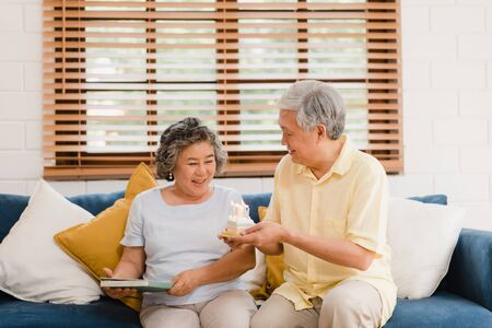 Asian elderly couple man holding cake celebrating wife's birthday in living room at home. Japanese couple enjoy love moment together at home. Lifestyle senior family at home concept.
