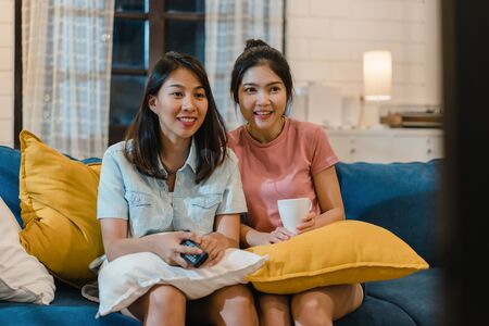 Lesbian women couple watching television at home, Asian female lover feeling happy funny moment looking drama entertainment together on sofa in living room in night concept.