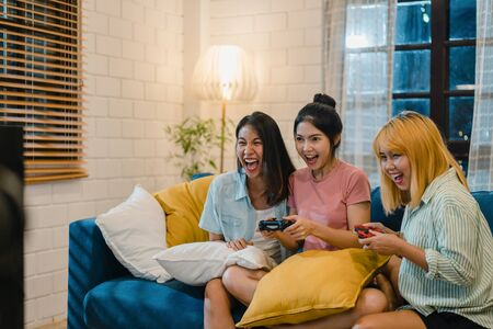 Group of Asian women couple play games at home, female using joystick having funny moment together on sofa in living room in night. Teenager young friend football fan, celebrate holiday concept. Banco de Imagens - 129703353