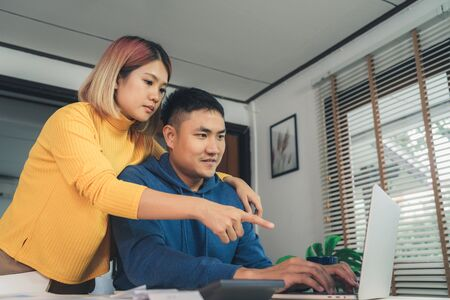 Young asian couple managing finances, reviewing their bank accounts using laptop computer and calculator at modern home. Woman and man doing paperwork together, paying taxes online on notebook pc. Archivio Fotografico - 129915214