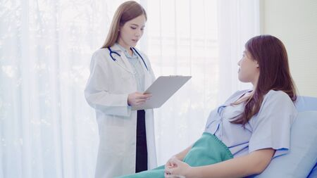 Beautiful smart Asian doctor and patient discussing and explaining something with clipboard in doctor hands while staying on Patients bed at hospital. Medicine and health care concept. Stock fotó