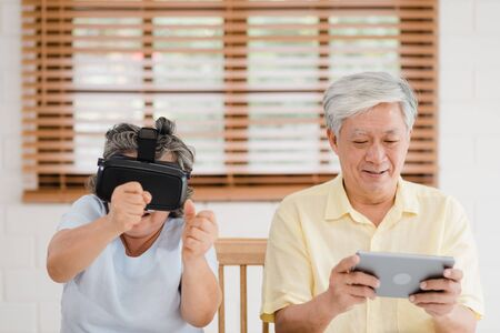 Asian elderly couple using tablet and virtual reality simulator playing games in living room, couple feeling happy using time together lying on table at home. Lifestyle Senior family at home concept. Stock fotó