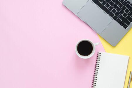 Kreatives flaches Lagefoto des Arbeitsplatzschreibtisches. Draufsichtschreibtisch mit Laptop, leeren leeren Notizbüchern und Kaffeetasse auf Pastellfarbhintergrund. Draufsicht mit Kopienraum, flache Lagephotographie. Standard-Bild