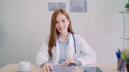 Confident Asian female doctor sitting at office desk and smiling at camera, health care and prevention concept in medical office.