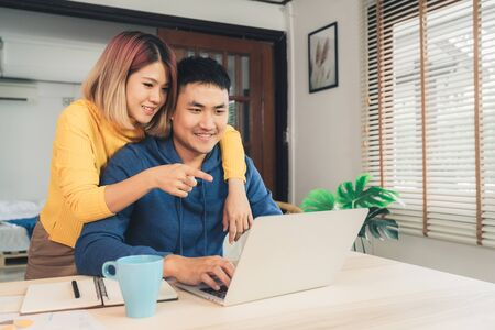 Young asian couple managing finances, reviewing their bank accounts using laptop computer and calculator at modern home. Woman and man doing paperwork together, paying taxes online on notebook pc. Archivio Fotografico - 129915314