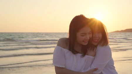 Young Asian lesbian couple kissing near beach. Beautiful women lgbt couple happy relax enjoy love and romantic moment when sunset in evening. Lifestyle lesbian couple travel on beach concept. Reklamní fotografie