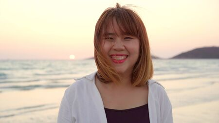 Young Asian woman feeling happy on beach, beautiful female happy relax smiling fun on beach near sea when sunset in evening. Lifestyle women travel on beach concept.