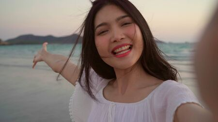 Blogger Asian woman record vlog video on beach, young beautiful female happy using mobile phone make vlog video on beach near sea when sunset in evening. Lifestyle women travel on beach concept.