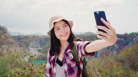 Asian backpacker woman selfie on top of mountain, young female happy using mobile phone taking selfie enjoy holidays on hiking adventure. Lifestyle women travel and relax concept.