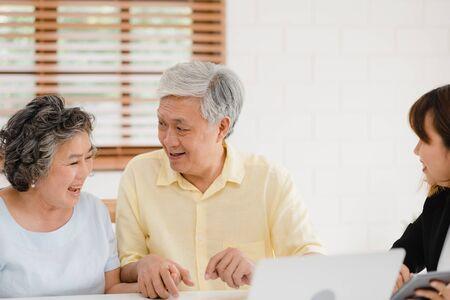 Asia Smart Female Agent bietet Krankenversicherungen für ältere Paare per Dokument, Tablet und Laptop an. Altes asiatisches Paar, das sich mit einem Versicherungsagenten berät, während es zu Hause zusammensitzt