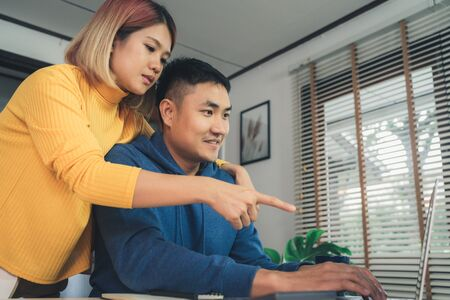 Young asian couple managing finances, reviewing their bank accounts using laptop computer and calculator at modern home. Woman and man doing paperwork together, paying taxes online on notebook pc. 免版税图像