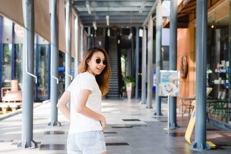 Traveler backpacker asian woman travel in Bangkok, Thailand. Happy young female spending holiday trip at amazing landmark and enjoy her journey in traditional city.