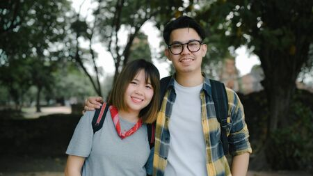 Traveler Asian couple feeling happy smiling to camera holiday trip at Thailand, backpacker sweet couple enjoy their journey at amazing landmark in traditional city. Portrait looking at camera.
