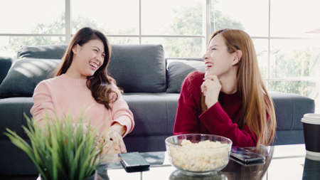 Asian women using smartphone and eating popcorn in living room at home, group of roommate friend enjoy funny moment while lying on the sofa. Lifestyle women relax at home concept.