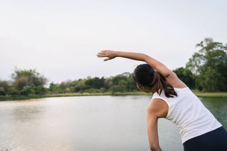 Healthy young Asian runner woman warm up the body stretching before exercise and yoga near lake at park under warm light morning. Lifestyle fitness and active women exercise in urban city concept. Stok Fotoğraf