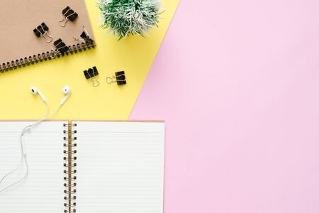 Creative flat lay photo of workspace desk. Top view office desk with blank notebooks, plant, earphone and copy space on pastel color background. Top view with copy space, flat lay photography. Stok Fotoğraf
