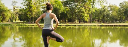 Young asian woman yoga outdoors keep calm and meditates while practicing yoga to explore the inner peace. Yoga have good benefits for health near lake at park. Panoramic banner background.