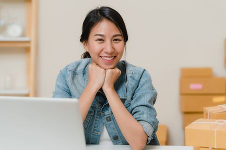 Business woman feeling happy smiling and looking to camera while working in her office at home. Beautiful Asian young entrepreneur owner of SME with small business owner at home office concept.