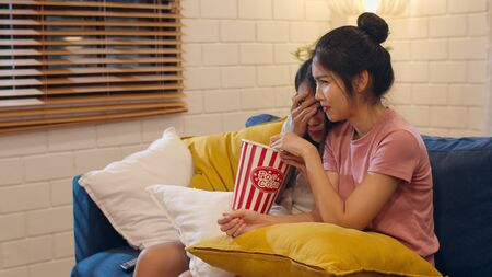 Lesbian lgbt women couple watching movie at home, Asian female lover eating popcorn scary and shock while looking horror film together on sofa in living room in night concept. Stock Photo