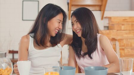 Asian Lesbian lgbtq women couple have breakfast at home, Young Asia lover female feeling happy drink juice, corn flakes cereal and milk in bowl on table in kitchen in the morning concept.