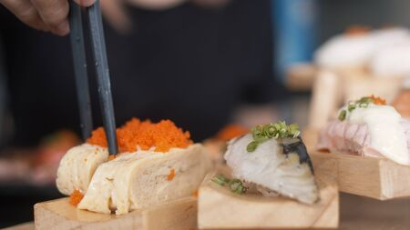 Asian woman eating sushi in japanese restaurant, young female holding chopsticks and eating salmon sushi in lunch time in summer. Lifestyle women eating traditional food concept.