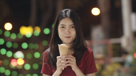 Asian young woman travel in Bangkok, Thailand, beautiful female feeling happy walking and eating ice cream at The Khao San Road. Women travel eat street food in Thailand concept.