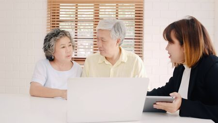 Asia smart female agent offers health insurance for elderly couples by document, tablet and laptop. Aged Asian couple consulting with insurance agent while sitting together with at home.
